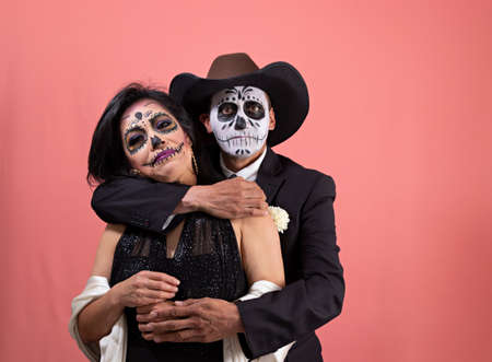 A couple disguised as a catrin and catrina, while he is giving flowers to her posing with a plain background Standard-Bild