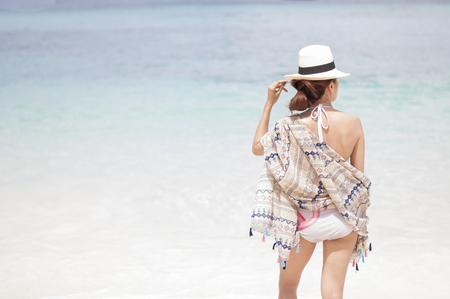 sunhat: Woman in bikini at tropical beach Stock Photo