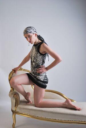woman kneeling: Woman kneeling on chaise lounge Stock Photo