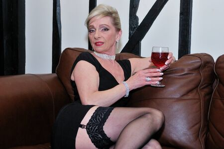 Older woman in stockings with wine
