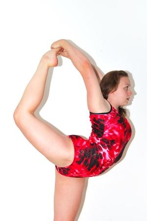 Pretty gymnast in red balanced on one leg Stock Photo - 9774926