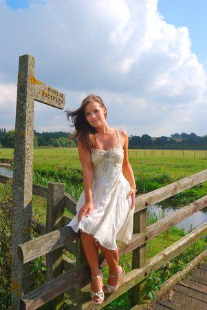 pretty girl sitting near footpath sign photo
