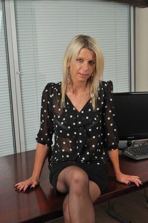 机の上に座っている魅惑的な女性実業家 写真素材