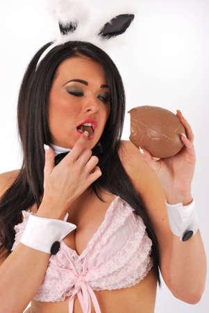 セクシーなバニー女の子チョコレートの卵を食べる