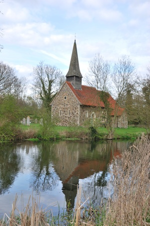 english countryside: small church reflecting in river Stock Photo
