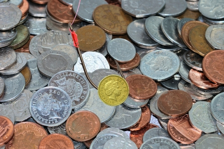 Pound coin as bait with coins in background Stock Photo - 16392493