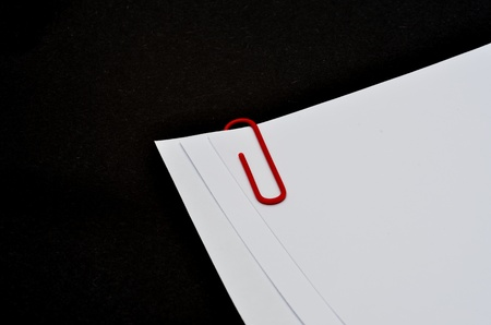 Paper clip on white paper with black background photo