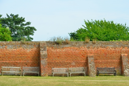 Wooden benches against brick wall photo