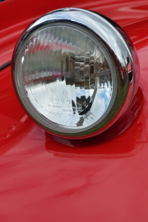 Detail of car headlamp on red in portrait photo
