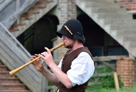 Man playing medieval wooden flute