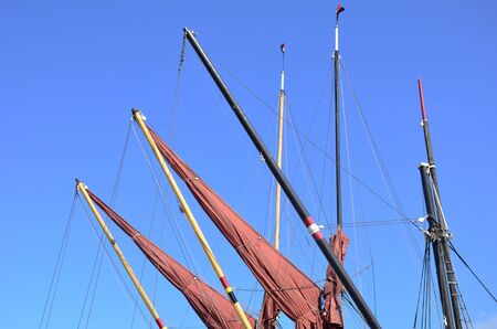 furled: Red sails furled on jibs Stock Photo