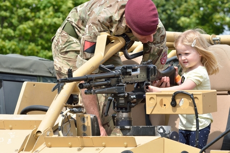 Military Tattoo  COLCHESTER ESSEX UK 8 July 2014:   Small Girl being shown gun by soldier
