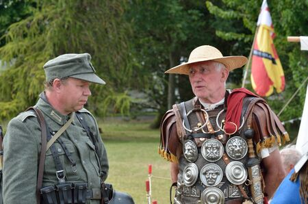 anachronistic: Military Tattoo  COLCHESTER ESSEX UK 8 July 2014:   Roman soldier chatting to German soldier in re-enactmentl