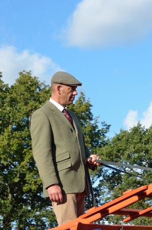 reins: IPSWICH SUFFOLK  UK  25 October 2014:  East Anglia Equestrian Fair English countryman holding reins of Carthorse Editorial