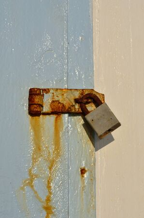 Old padlock on blue wooden background photo