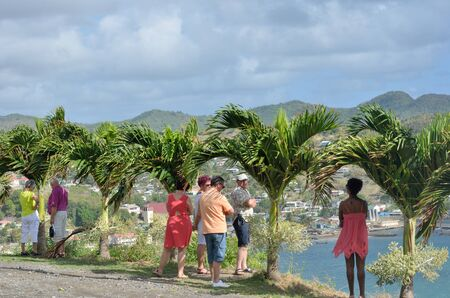 st lucia: DENNERY  ST LUCIA CARIBBEAN 19  January  2015: Tourists looking over small Caribbean Town