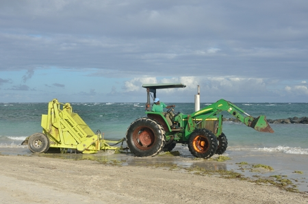 st lucia: ST LUCIA CARIBBEAN 17  January  2015: Surf rake on tractor by sea Editorial