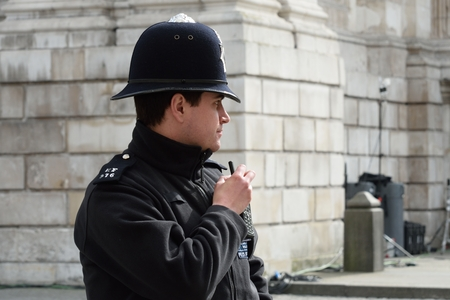 CITY OF LONDON ENGLAND 13 March 2015:  English Policeman with radio