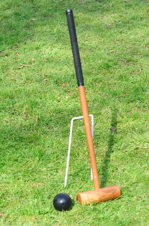 leaning against: Croquet Mallet leaning against hoop