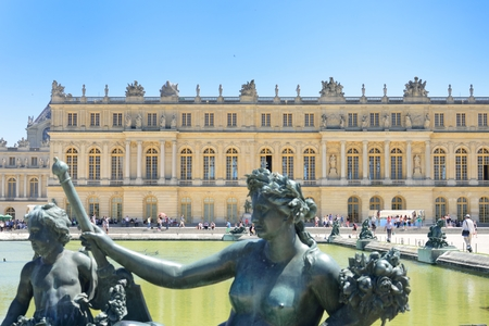 versailles: VERSAILLES PARIS FRANCE 6 JUNE  2015:Statue in fountain in front of Palace of Versailles Editorial