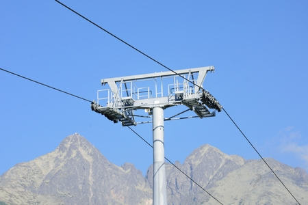 chair on the lift: Chair lift mechanism with mountain in background