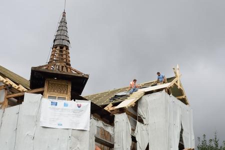 renovate old building facade: TATRAS SLOVAKIA  26 AUGUST  2015: Men restoring Church Roof as part of European funding
