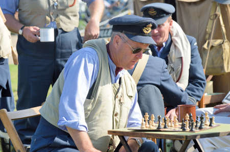 world war two: DUXFORD CAMBRIDGESHIRE UK 20 August 2015:Man concentrating on  chess awaiting scramble in World War Two reenactment Editorial