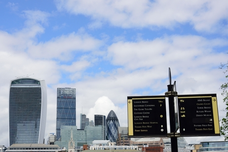 southbank: THAMES SOUTHBANK LONDON  ENGLAND 2 May  2015:  Looking towards Canary Wharf with sign in foreground