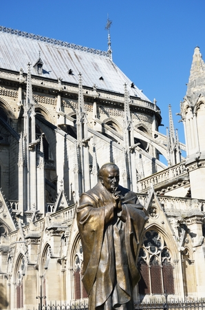 pontiff: Statue of John Paul II with Notre Dame in Background