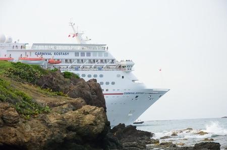 éxtasis: AMBAR ENSENADA REPÚBLICA DOMINICANA 9 DE FEBRERO DE 2016: barco de Carnival Cruise éxtasis que sale del acceso con rocas en primer plano