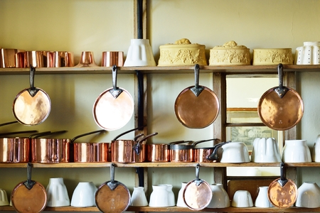 antique dishes: Copper pots and pans on Wall Stock Photo