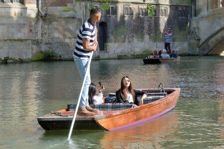 punt: Cambridge England, United Kingdom -May 20, 2016: Punter guiding asian  tourists on Cam Cambridge England