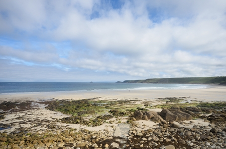 sennen: Empty Beach with stones in foreground and blue and cloudy skies Stock Photo