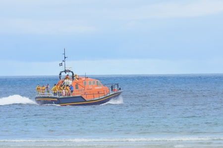 sennen: Sennen Cove Cornwall , United Kingdom - July 02, 2016:  RNLI lifeboat heading out to sea Editorial