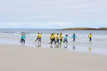 sennen: Sennen Cove Cornwall , United Kingdom - July 02, 2016: Group of young children running out to sea for surfing lesson