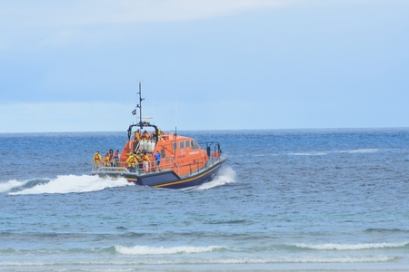 sennen: Sennen Cove Cornwall , United Kingdom - July 02, 2016:  RNLI lifeboat heading out to the  sea Editorial