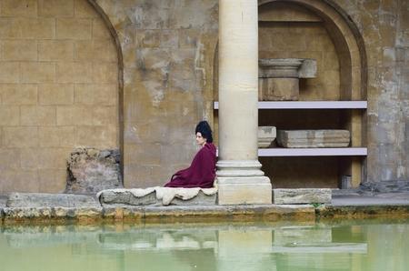 roman pillar: Bath Somerset , United Kingdom - June 30, 2016: Woman in Roman costume next to pillar  recreating scene at the Roman Baths in centre of city