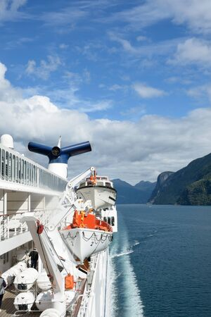lifeboats: Geirangerfjord  Norway -  July  31, 2016: View of Geirangerfjord  Norway from rear of cruise ship Magellan with lifeboats and funnel