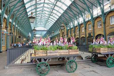 Covent Garden London England, United Kingdom - August 16, 2016: Central Piazza Convent Garden with Flower Cart in Foreground Editorial