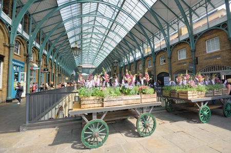 covent: Covent Garden London England, United Kingdom - August 16, 2016: Central Piazza Convent Garden with Flowers on cart  in Foreground Editorial