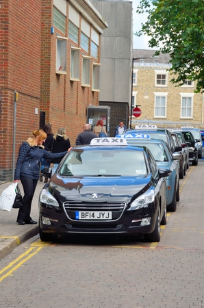hailing: Canterbury  , United Kingdom - September 30, 2016: Woman at English Taxi Rank talking to driver