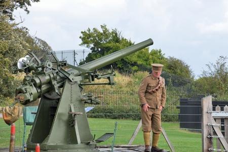 anti war: Dover, United Kingdom - October 1, 2016: Man firing world war two  static anti aircraft gun in re-enactment