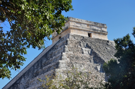 Temple at Chichen Itza Mexico with tree in foreground 写真素材