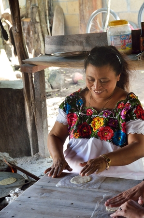 Coba  , Mexico - January  19, 2017:  Woman making Tortillas in traditional way