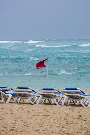 Empty sunbeds on windy resort beach and warning flag