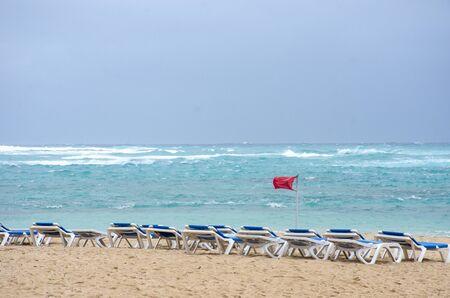 Row of Empty sunbeds on windy dangerous beach