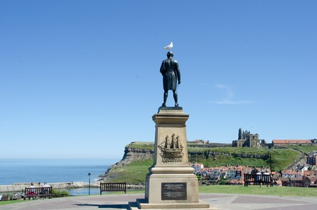 Whitby Yorkshire UK  - 25 June 2018:  Statue of Captain Cook overlooking town of Whitby