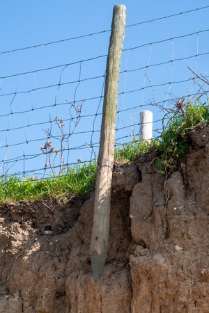 Exposed fence post on coastal path as a result of sea erosion