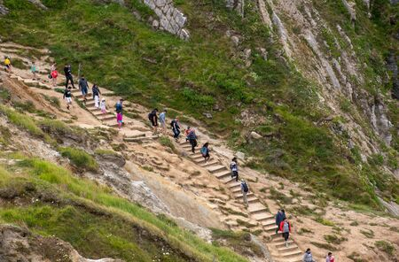 Lulworth Dorset United Kingdom 21 July 2019  -:   Walkers stepping to beach at Durdle Door Editöryel