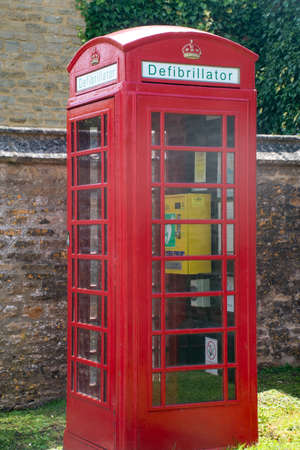 Traditional British Telephone Box in village converted to defibrillator Banque d'images
